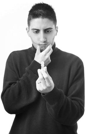 Monochrome d'un homme r�fl�chi �tudier une pi�ce d'�checs dans sa main pendant qu'il �labore une strat�gie, un studio sur fond blanc