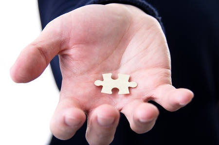 hand offering a puzzle piece to end the puzzle, the solution to the problem photo