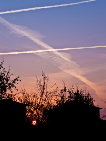 criss: The glowing sun setting between two houses with beautiful soft oranges and violet in the sky which is criss crossed by contrails. Stock Photo