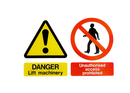 Two isolated warning hazard signs, one of an exclamation mark on a yellow triangle for lift machinery, and one prohibiting unauthorised acces with a man walking in a red circle Stock Photo - 12713815
