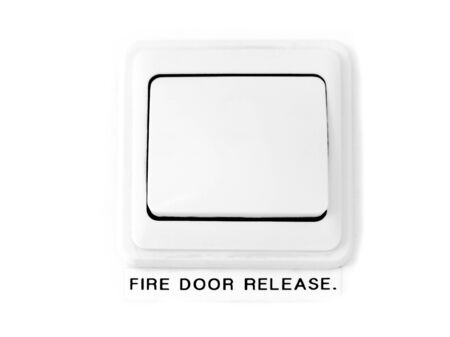 Closeup of a rectangular white fire door release button on a white door  photo