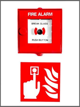 Bouton d'alarme d'incendie enferm� dans le verre sur un signe montrant un doigt appuyant sur le bouton pr�s des flammes sur un mur blanc