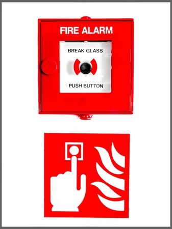 Fire alarm button encased in glass over a sign showing a finger pushing the button near flames on a white wall photo