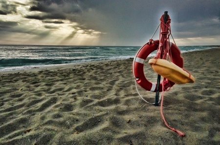 flotation: Rescue equipment with a life ring or preserver and a flotation stretcher hanging on a pole on a beach under a stormy sky Stock Photo