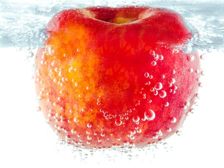 Ripe red apple being submerged underwater trapping shiny round air bubbles on the skin Stock Photo - 13928446