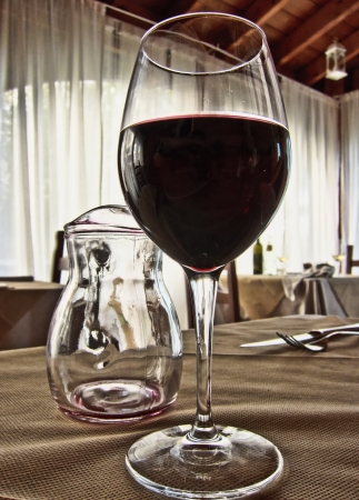 Empty serving pitcher on a table holding a lone glass filled with grape juice photo