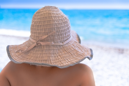 Rear view of a woman in a sunhat with her face completely obscured sitting on a tropical beach protecting her skin from harmful ultraviolet rays