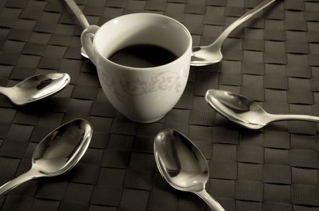 Coffee and teaspoons still life with a freshly brewed cup of aromatic filter coffee surrounded by six silver spoons in a radiating pattern photo