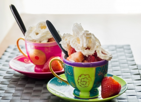 piped: Serving of fresh strawberries and icecream or whipped piped cream in two colourful ceramic cups and saucers