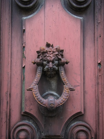 Old doorknocker with the garlanded head of a man or demon mounted on an old wooden door with a light coating of pink paint Stock Photo