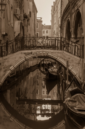 Sepia toned image of vintage Venice with a quaint stone bridge crossing a canal with gondolas and a mirrored reflection
