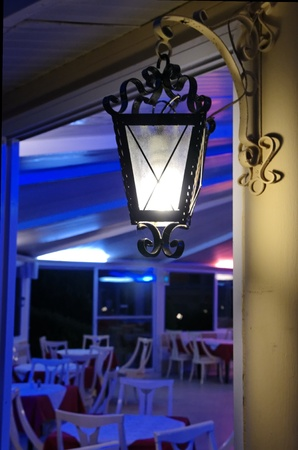 Illuminated wall mounted lantern light at the entrance to a catering venue with chairs and tables photo