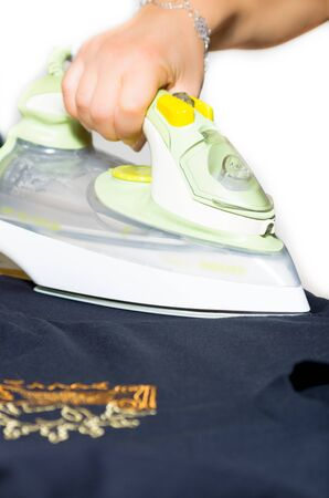 Person completeing the daily household chores with a closeup of a hand doing the ironing Stock Photo - 15147949