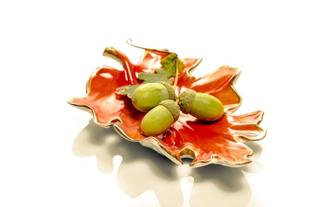 changing seasons: Autumn still life with acorns on a glazed ceramic dish in the shape of a red fall oak leaf conceptual of the changing seasons on a white background with reflection Stock Photo