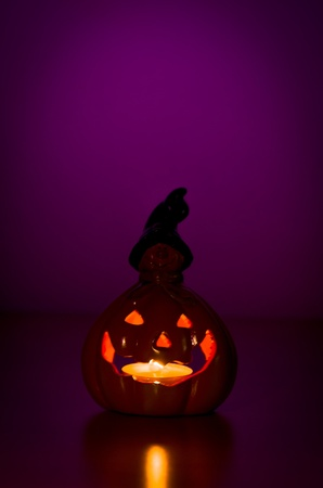 Glowing halloween pumpkin lantern casting an eerie evil light in the darkness of a purple night with copyspace photo