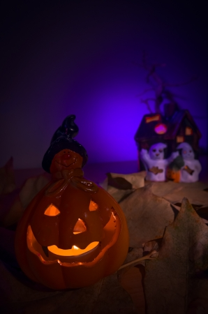 Glowing Halloween pumpkin with an evil face on rocks against a purple midnight sky with eerie little ghosts and ghouls in the background photo