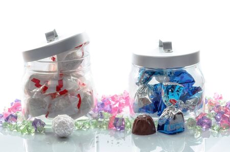 Two glass jars of luxury foil wrapped Christmas chocolates with delicious unwrapped examples displayed in the foreground for your festive greeting card photo