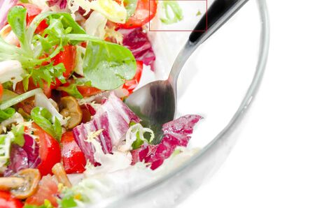 Closeup of a fresh mixed leaf and tomato salad in a glass bowl with stainless steel serving spoon  Cropped studio shot over white Stock Photo