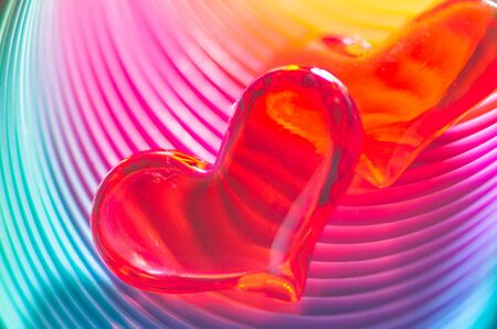 Beautiful translucent red Valentine hearts inside a brightly coloured festive spiral tube in the colours of the rainbow for a dramatic effect