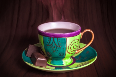 Colourful green cup of freshly brewed hot tea served with luxury chocolates on the saucer against a dark background with copyspace photo