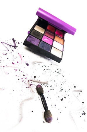 squiggles: Artistic arrangement of colourful eye makeup in a box with an applicator and scattered remnants and squiggles of powdered cosmetic in the foreground on white