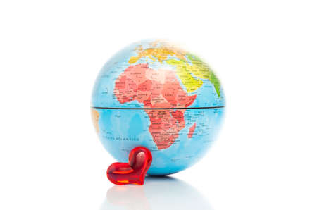 Conceptual image of a colourful globe showing a map of Africa with a small shiny red heart in front of it on a white background