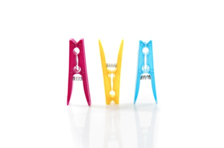 A pink, yellow and blue plastic clothes pegs side by side against a white background  Stock Photo