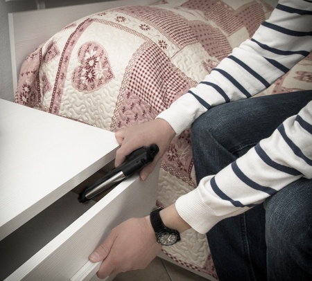 Man in a high crime area placing a handgun into the drawer of a bedside table in readiness to defend himself during a home invasion or attack and to ensure a good nights sleep Stock Photo