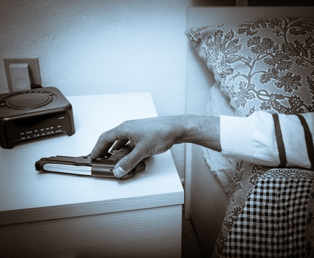 Man lying in bed with his hand holding a handgun lying at the ready on a bedside table to ensure the safety and security of his family in the event of a home break in in a high crime area photo
