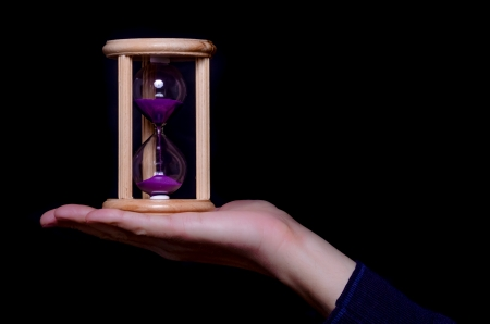 Hand holding an egg timer balanced on an open extended palm filled with colourful purple sand running through the glass against a dark studio background Stock Photo