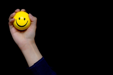 Male hand holding a yellow smiley ball emoticon with a big happy smile on a dark studio background with copyspace Stock Photo