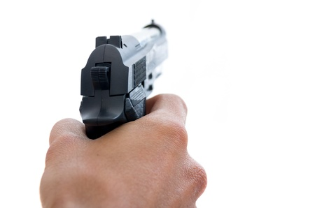 Closeup view from behind of a male hand holding a pistol taking aim away from the camera with shallow depth of field on a white background Stock Photo