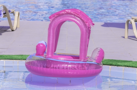 flotation: Pink plastic ring with an upper tube floating in a cool refreshing swimming pool ready for a small child to come and play