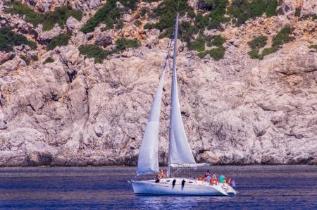 Les personnes b�n�ficiant d'une croisi�re sur un voilier plaisir pass� la base d'une falaise marine rocheux sur un jour d'�t� ensoleill�