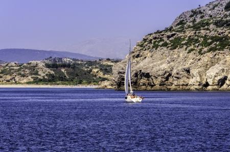 Yacht charg� de vacanciers naviguant vers un �lot rocheux � travers un oc�an bleu calme Banque d'images