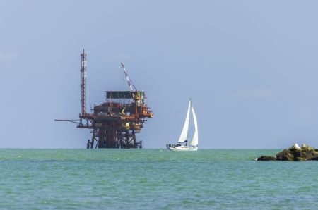 Pretty white yacht sailing past an offshore oil platform on a sunny summer day on a calm sea