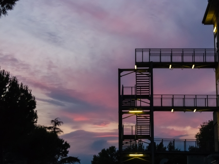 Fire escape or external metal stairway on the exterior facade of a multistorey building silhouetted against a colourful sunset sky in shades of pink and purple photo