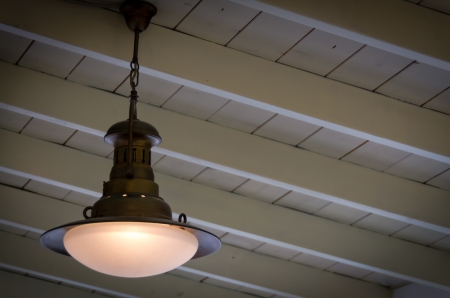 Illuminated metal light fitting with a glass globe hanging from a wooden ceiling with beams and copyspace Stock Photo