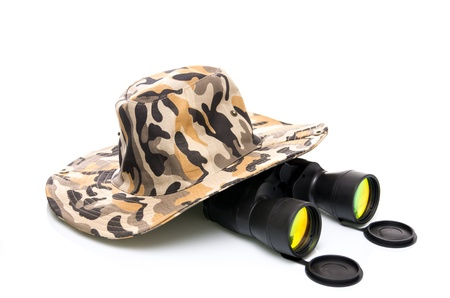 Binoculars and a safari hat on a white background conceptual of travel, adventure and eco-tourism or a wildlife safari photo