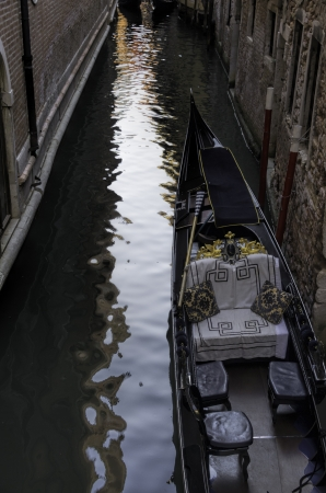 High angle view of a romantic empty gondola floating on a narrow Venetian canal showing the sumptuous love seat with additional seating for more passengers in Venice, Italy Stock Photo - 20275799