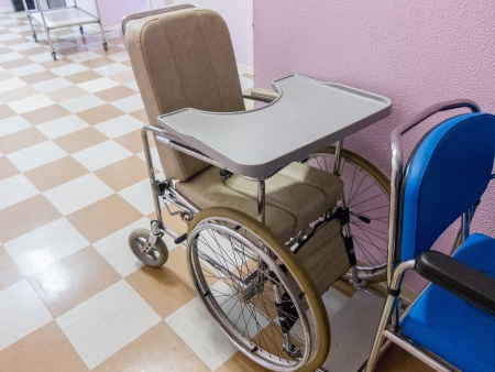 requiring: Empty wheelchair in a hospital corridor waiting for the the admission of an emergency or disabled patient requiring assistance for mobility