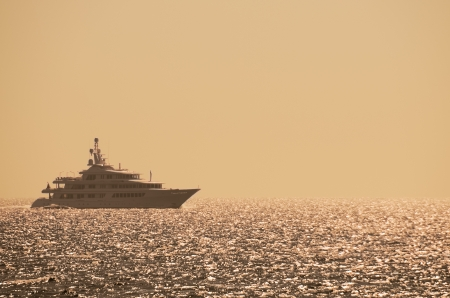 Yacht de luxe de croisi�re sur une mer calme au coucher du soleil ou le lever du soleil avec un ciel lumineux et les reflets sur la surface de l'eau