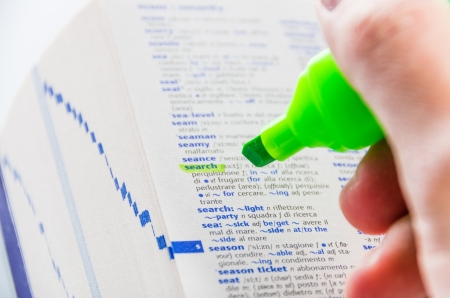derivation: Close-up of a man hands using a florescent green marker to highlight the Search word on a dictionary