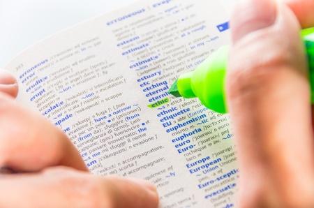 Gros plan d'un homme les mains � l'aide d'un marqueur fluorescent vert pour mettre le mot d'�thique sur un dictionnaire