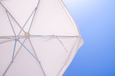 Under a white beach umbrella looking up into the opened parasol with its metal spokes against a blue sunny sky