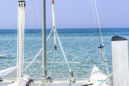 Gros plan d'un voilier catamaran blanc amarr� contre un oc�an tropical bleu calme sous le soleil d'�t�