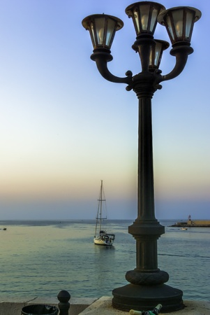 Silhouette of an ornate lamppost with a departing yacht leaving the harbour and sailing towards the sunset Stock Photo