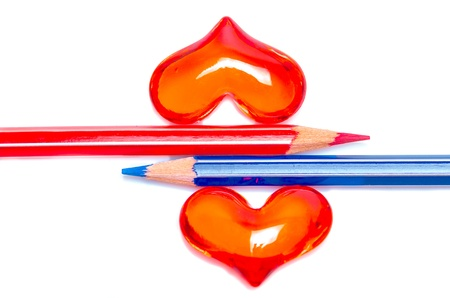 Conceptual image with red and blue coloured pencils to signify the sexes placed together between two romantic Valentine hearts on a white background photo