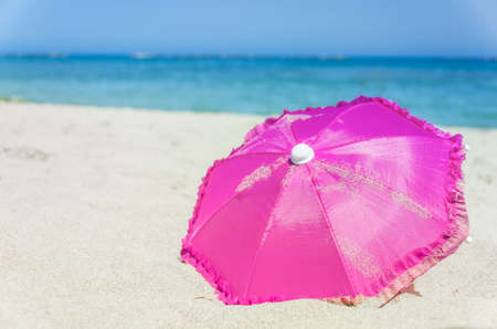 Pretty vibrant pink beach umbrella on the beautiful golden sand of an idyllic tropical beach conceptual of a summer vacation or getaway