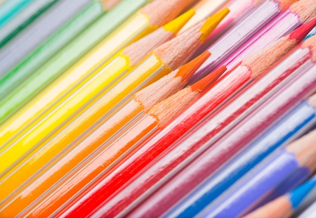 Background of rainbow coloured wooden pencil crayons arranged diagonally with a close up view of the tips